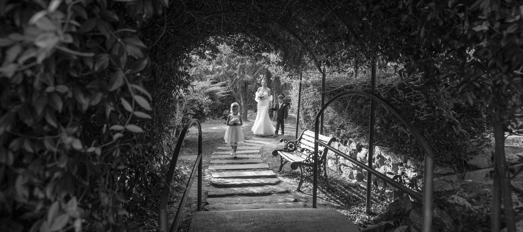 Foto del matrimonio di Paola e Fabio mentre la sposa sta per passare sotto al pergolato assieme ai figli
